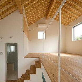 Imagen de salón para visitas tipo loft, minimalista, pequeño, sin chimenea, con parades naranjas, suelo de contrachapado y suelo marrón