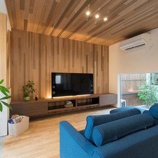 他の地域のモダンスタイルのおしゃれなリビング (マルチカラーの壁、淡色無垢フローリング、据え置き型テレビ、ベージュの床) の写真
