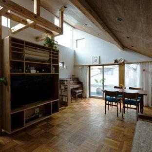 Imagen de biblioteca en casa abierta y machihembrado, moderna, pequeña, sin chimenea, con paredes blancas, suelo de madera en tonos medios, televisor colgado en la pared, suelo marrón y machihembrado