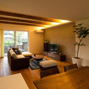 Esempio di un soggiorno etnico con pareti multicolore, pavimento in legno massello medio, TV autoportante e pavimento marrone