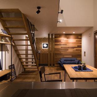 他の地域のインダストリアルスタイルのおしゃれなリビング (白い壁、無垢フローリング、据え置き型テレビ、茶色い床) の写真