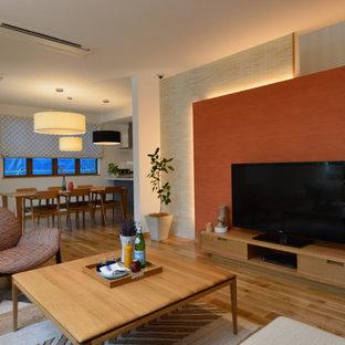 他の地域の広いモダンスタイルのおしゃれなLDK (オレンジの壁、無垢フローリング、暖炉なし、据え置き型テレビ) の写真