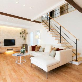 他の地域の広いコンテンポラリースタイルのおしゃれなLDK (白い壁、埋込式メディアウォール、茶色い床) の写真