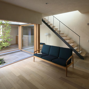 Foto di un soggiorno scandinavo con pareti bianche, pavimento in compensato, nessun camino, nessuna TV e pavimento grigio