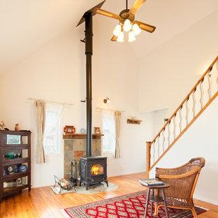 他の地域の中サイズのカントリー風おしゃれなLDK (フォーマル、白い壁、無垢フローリング、薪ストーブ、石材の暖炉まわり、テレビなし、茶色い床) の写真