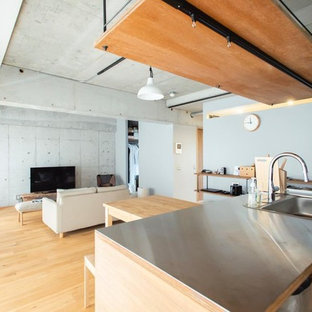 東京都下のインダストリアルスタイルのおしゃれなLDK (グレーの壁、淡色無垢フローリング、据え置き型テレビ、茶色い床) の写真