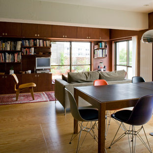 This is an example of a bohemian open plan living room in Tokyo with brown walls, medium hardwood flooring, no fireplace and a freestanding tv.