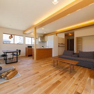 アジアンスタイルのおしゃれなLDK (白い壁、無垢フローリング、薪ストーブ、石材の暖炉まわり、茶色い床) の写真
