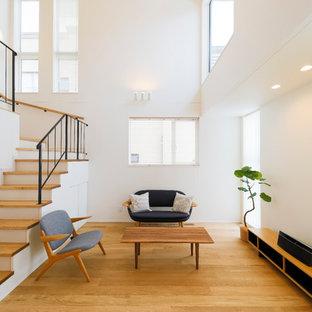 北欧スタイルのおしゃれなリビング (白い壁、無垢フローリング、茶色い床) の写真