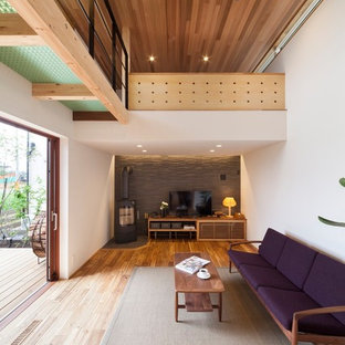 他の地域の小さいコンテンポラリースタイルのおしゃれなリビング (白い壁、薪ストーブ、据え置き型テレビ、茶色い床) の写真