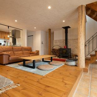 Foto de salón abierto, campestre, con paredes beige, suelo de madera clara, estufa de leña, marco de chimenea de baldosas y/o azulejos y suelo multicolor