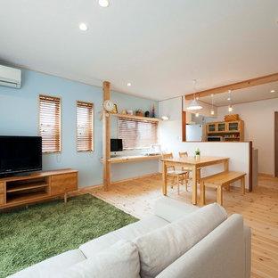 他の地域のアジアンスタイルの居間の画像 (青い壁、淡色無垢フローリング、据え置き型テレビ、茶色い床)