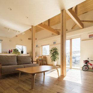 他の地域のモダンスタイルのおしゃれなLDK (フォーマル、白い壁、無垢フローリング、薪ストーブ、タイルの暖炉まわり、据え置き型テレビ、茶色い床) の写真
