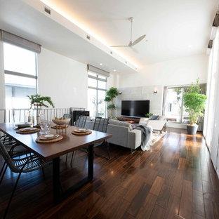 Modelo de salón para visitas abierto, moderno, grande, con paredes blancas, suelo de contrachapado y televisor independiente