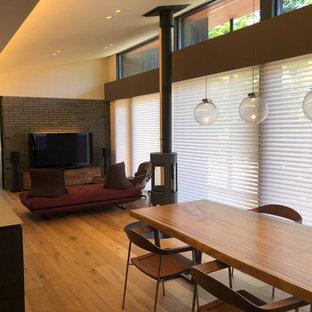 他の地域の中くらいのモダンスタイルのおしゃれなLDK (グレーの壁、淡色無垢フローリング、薪ストーブ、金属の暖炉まわり、ベージュの床、ミュージックルーム、据え置き型テレビ) の写真
