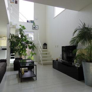 Inspiration för moderna allrum med öppen planlösning, med vita väggar, en fristående TV, plywoodgolv och grått golv