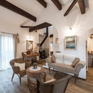 他の地域の中くらいの地中海スタイルのおしゃれな独立型リビング (白い壁、淡色無垢フローリング、薪ストーブ、レンガの暖炉まわり、茶色い床) の写真