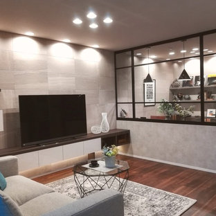 На фото: гостиные комнаты в стиле лофт с серыми стенами, полом из фанеры, отдельно стоящим ТВ и коричневым полом без камина