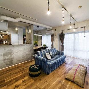 他の地域のインダストリアルスタイルのおしゃれなLDK (マルチカラーの壁、無垢フローリング、据え置き型テレビ、茶色い床) の写真