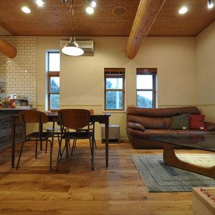 他の地域のラスティックスタイルのおしゃれなリビング (ベージュの壁、無垢フローリング、暖炉なし、据え置き型テレビ、ベージュの床) の写真