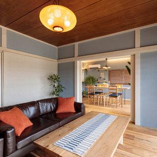 他の地域の小さいビーチスタイルのおしゃれなリビングのホームバー (青い壁、無垢フローリング、据え置き型テレビ、茶色い床) の写真
