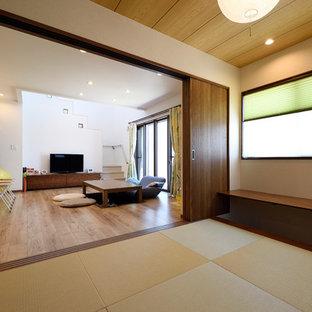 Modelo de salón abierto, asiático, de tamaño medio, con paredes blancas, tatami y suelo marrón