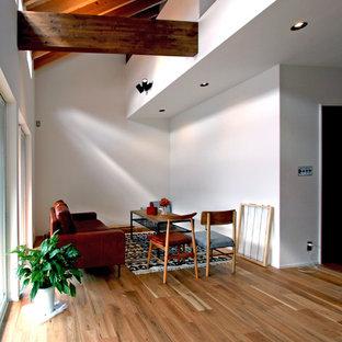 他の地域のモダンスタイルのおしゃれなLDK (フォーマル、白い壁、無垢フローリング、暖炉なし、壁掛け型テレビ、茶色い床) の写真