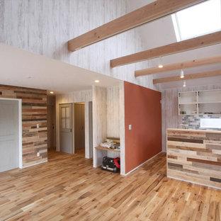 中サイズのビーチスタイルのおしゃれなLDK (オレンジの壁、無垢フローリング、コーナー設置型暖炉、レンガの暖炉まわり、マルチカラーの床) の写真