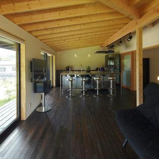 Idee per un soggiorno moderno aperto con angolo bar, pareti bianche, parquet scuro, nessun camino, TV a parete, pavimento nero e travi a vista