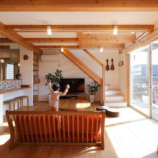 Foto di un piccolo soggiorno etnico aperto con pareti bianche, TV autoportante, pavimento in legno massello medio e nessun camino