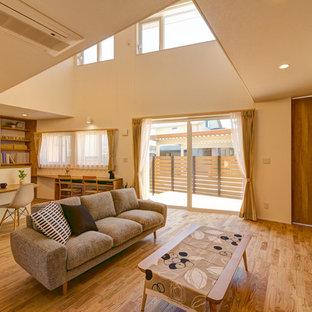 Cette image montre un salon asiatique ouvert avec un mur blanc et un sol en bois brun.