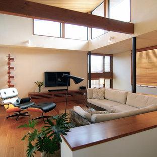 Offenes Mid-Century Wohnzimmer ohne Kamin mit braunem Holzboden, Wand-TV, braunem Boden und weißer Wandfarbe in Sonstige