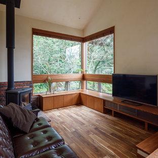 他の地域のアジアンスタイルのおしゃれなLDK (白い壁、濃色無垢フローリング、据え置き型テレビ、茶色い床、薪ストーブ) の写真