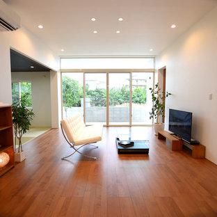 他の地域のモダンスタイルのおしゃれなLDK (白い壁、合板フローリング、暖炉なし、据え置き型テレビ、茶色い床) の写真