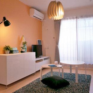 Foto di un piccolo soggiorno scandinavo aperto con pareti arancioni, pavimento in compensato e TV autoportante