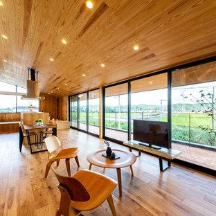 他の地域の広いコンテンポラリースタイルのおしゃれなLDK (茶色い壁、無垢フローリング、据え置き型テレビ、茶色い床) の写真