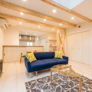 На фото: парадные, открытые гостиные комнаты в восточном стиле с белыми стенами, полом из фанеры, отдельно стоящим ТВ и белым полом