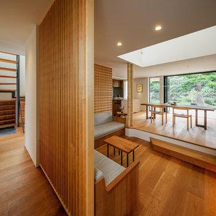 Diseño de salón abierto, machihembrado y ladrillo, minimalista, grande, ladrillo, con suelo de madera en tonos medios, televisor colgado en la pared y ladrillo