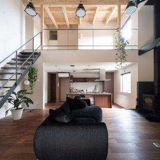 他の地域のアジアンスタイルのおしゃれなLDK (ベージュの壁、濃色無垢フローリング、薪ストーブ、コンクリートの暖炉まわり、据え置き型テレビ) の写真