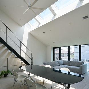 Modelo de salón abierto, moderno, con paredes blancas, suelo de contrachapado, televisor colgado en la pared y suelo gris