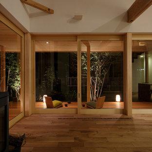 Idee per un soggiorno etnico con pareti bianche, pavimento in legno massello medio, stufa a legna e nessuna TV