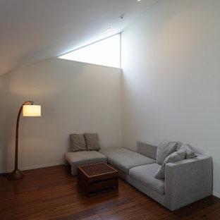Imagen de biblioteca en casa cerrada, moderna, pequeña, sin chimenea, con paredes blancas, suelo de contrachapado, marco de chimenea de ladrillo, televisor independiente y suelo marrón