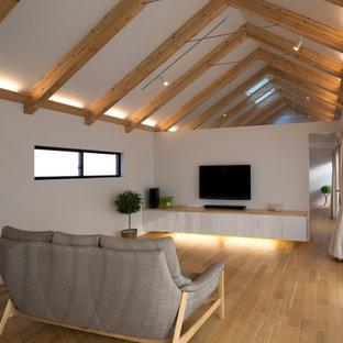 Foto de salón abierto, nórdico, de tamaño medio, con paredes blancas, suelo de contrachapado y televisor colgado en la pared