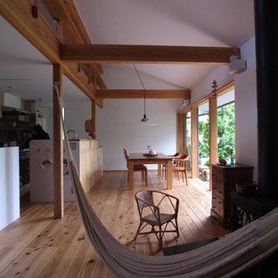 他の地域の中サイズの和風のおしゃれなLDK (白い壁、無垢フローリング、薪ストーブ、金属の暖炉まわり、テレビなし、茶色い床) の写真