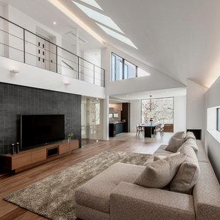 Ejemplo de salón abierto, contemporáneo, con paredes blancas, suelo de madera en tonos medios, suelo marrón y televisor colgado en la pared