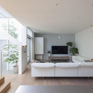 他の地域のモダンスタイルのおしゃれなLDK (マルチカラーの壁、塗装フローリング、壁掛け型テレビ、茶色い床) の写真