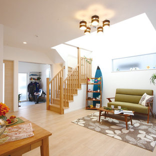 Example of a coastal open concept plywood floor and beige floor living room design in Other with white walls