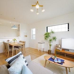 Offenes Skandinavisches Wohnzimmer mit weißer Wandfarbe, Sperrholzboden, beigem Boden und freistehendem TV in Sonstige