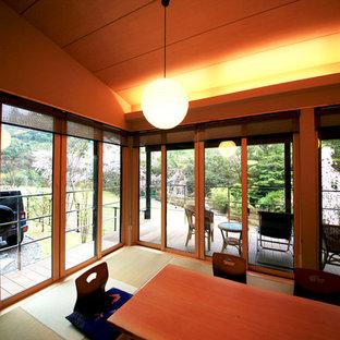 他の地域の巨大な和風のおしゃれなリビング (ベージュの壁、畳、据え置き型テレビ、緑の床) の写真