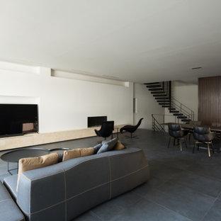 大阪のモダンスタイルのおしゃれなLDK (白い壁、据え置き型テレビ、グレーの床、板張り壁) の写真